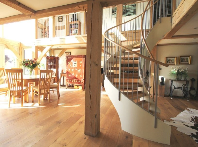 A great room featuring hardwood flooring and a two-storey ceiling, together with a spiral staircase with hardwood steps.