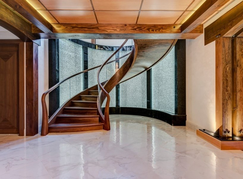 A majestic foyer boasting a stunning spiral staircase with hardwood steps and transparent glass railings. The area also has a gorgeous ceiling and classy tiles flooring.