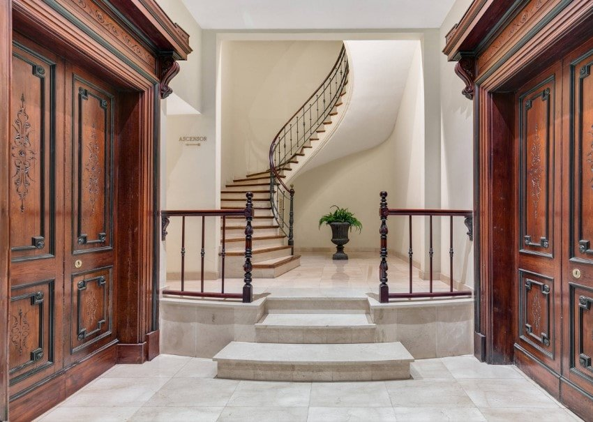 A foyer boasting elegantly-designed doors and a small straight stairs leading to the home's spiral staircase.