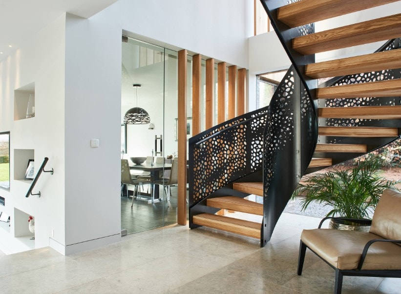 A focused look at this home's glamorous staircase with elegant black railings and hardwood steps.