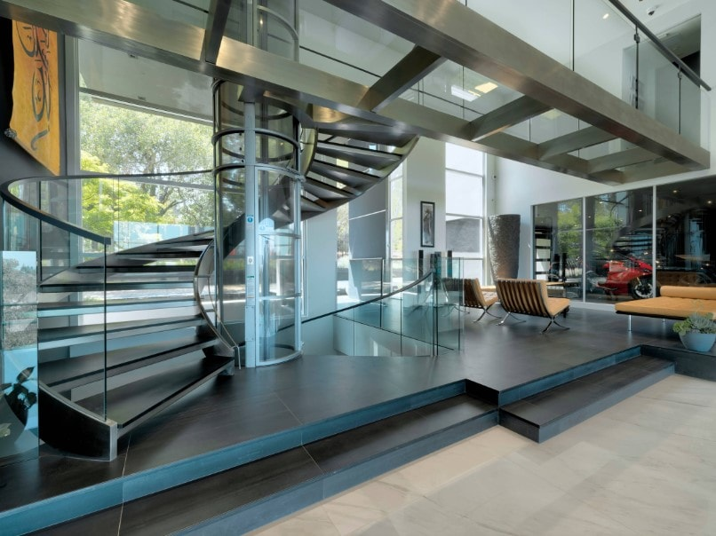 Contemporary house featuring a modern and stunning-looking spiral staircase with glass railings.
