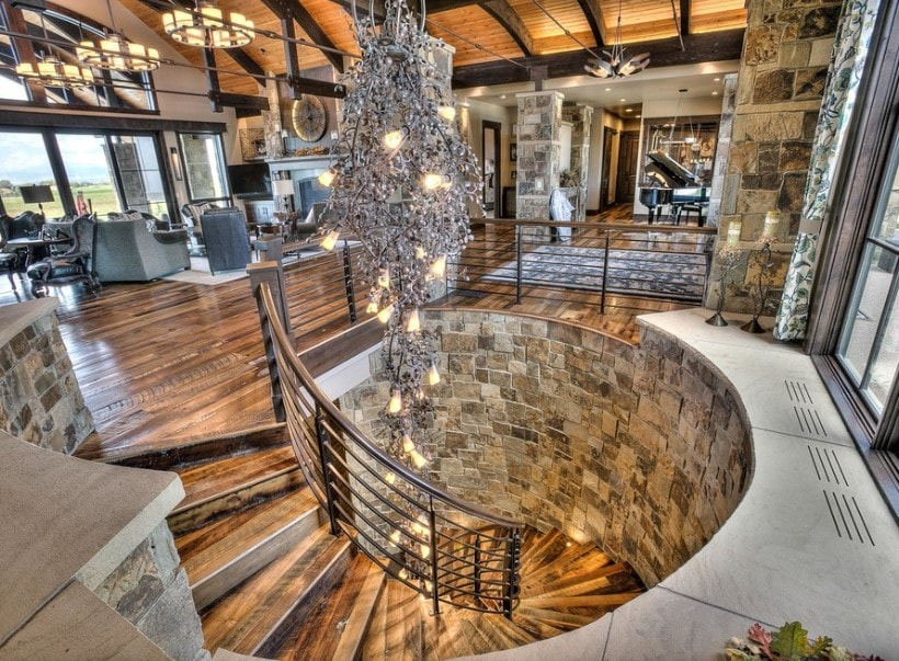 This home boasts hardwood floors and high wooden ceiling with exposed beams. There's a spiral staircase leading to the home's underground area lighted by a glamorous ceiling light.