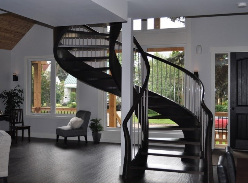 A close up look at this home's dark finished spiral staircase surrounded by white walls and a high ceiling.