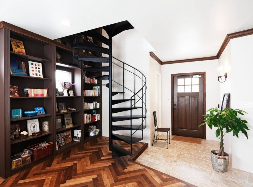 Foyer with stylish hardwood floors and built-in multiple shelving, together with a black spiral staircase.