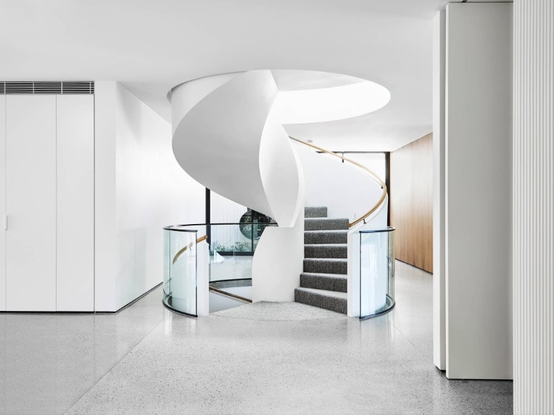 A focused shot at this home's staircase surrounded by white walls and white ceiling. This spiral staircase offers carpeted steps with white railings.