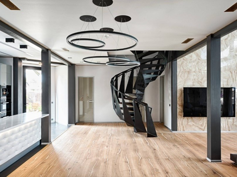 A spacious great room featuring a stylish ceiling and hardwood flooring, along with a very attractive black spiral staircase.