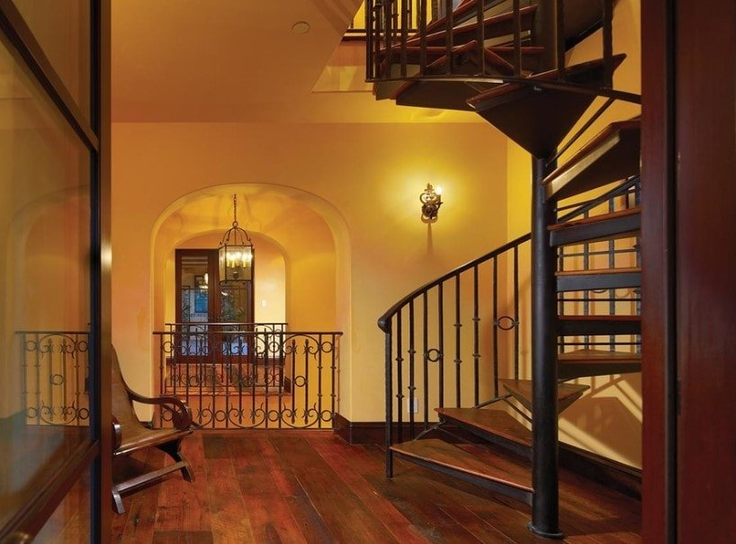 A Mediterranean home featuring hardwood floors and walls with wall lights. The home features a spiral staircase with iron railings.