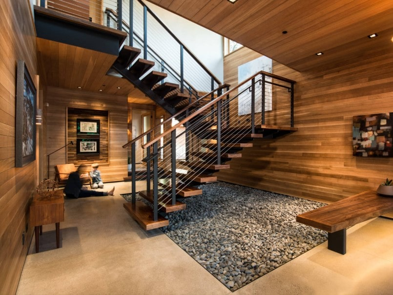 A modern rustic home boasting wooden walls and ceiling, along with a half-turn staircase with hardwood steps and handrails.