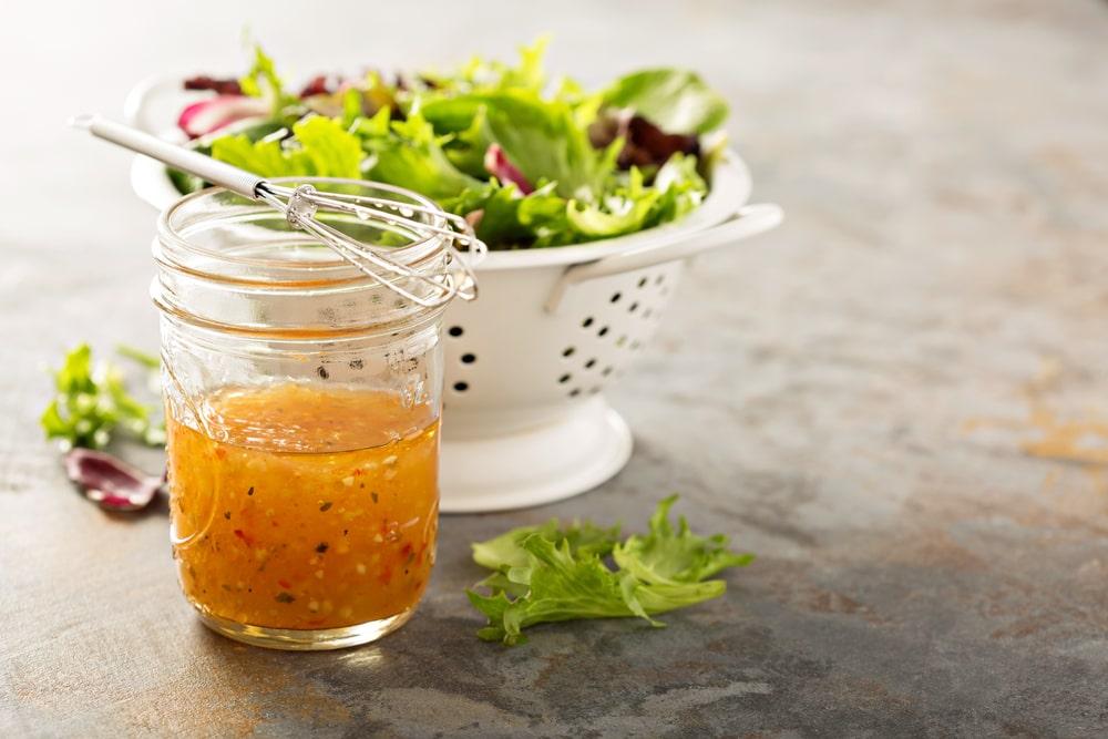 Italian dressing on a small jar beside a bowl of fresh salad.