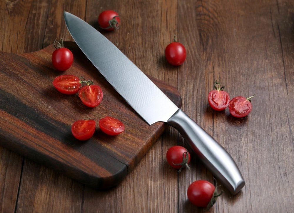Kitchen knife on a wooden cutting board surrounded by whole and sliced cherries.