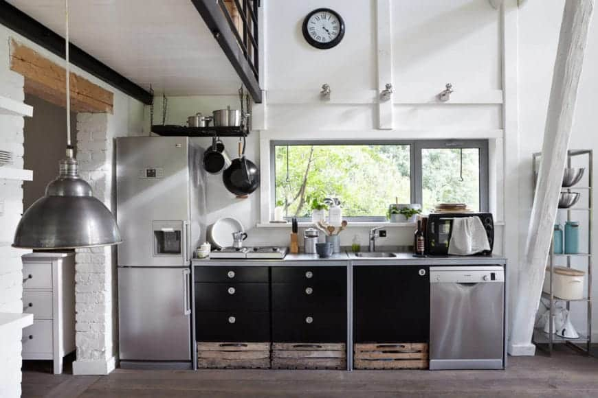 White kitchen contrasted by black cabinets and pot rack that hung above the stainless steel fridge. It has natural hardwood flooring and a glazed window that invites natural light in.