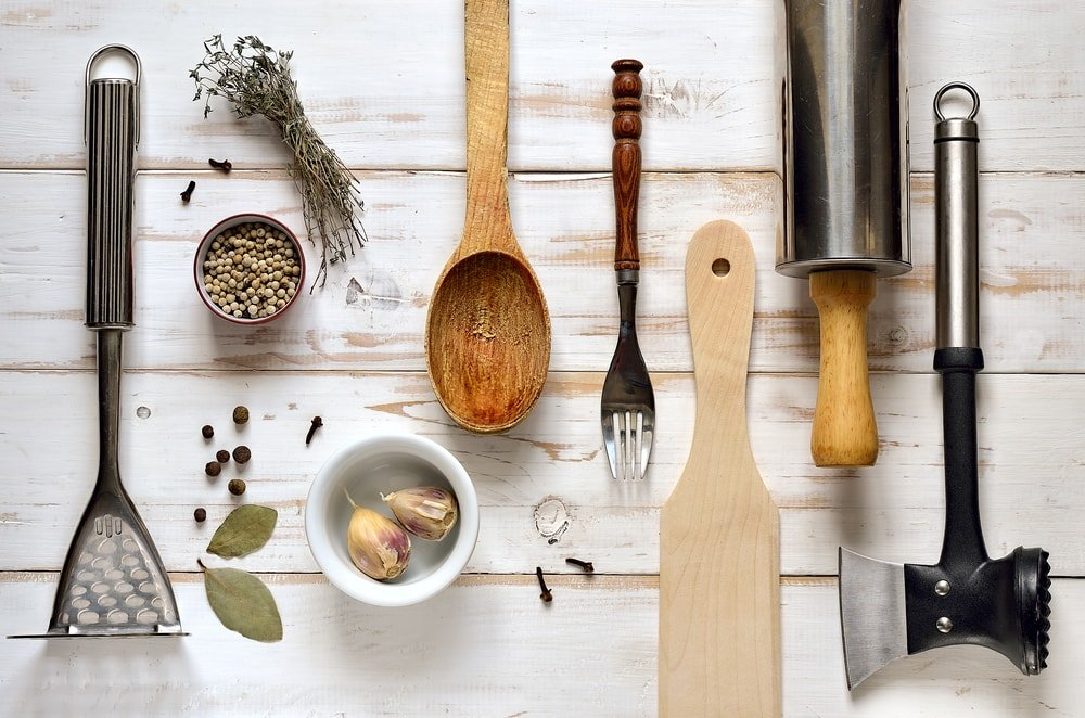 Flat lay of various kitchen utensils on a whitewashed wooden desk.