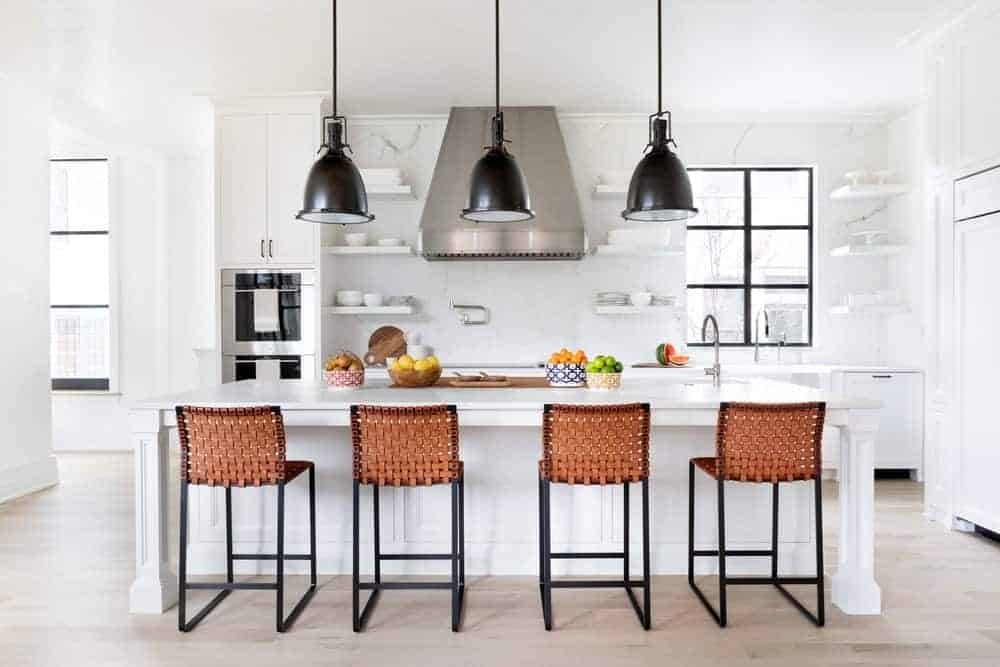 White kitchen contrasted by black dome pendants that hung over a breakfast island that's lined with woven counter chairs. It has floating shelves and a stainless steel range hood fixed against the marble backsplash.