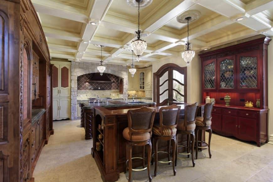 This kitchen offers two islands, one serves as a breakfast bar, both lighted by gorgeous pendant lights hanging from the beautiful coffered ceiling.