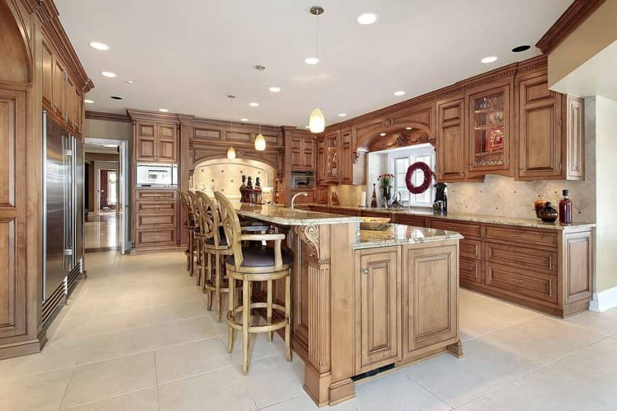 This kitchen features brown kitchen counters and cabinetry, along with a center island featuring a marble countertop and has a breakfast bar counter.