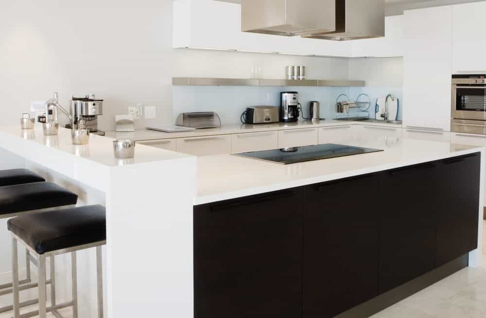 A close up look at this kitchen's island and a breakfast bar counter with modern bar seats.
