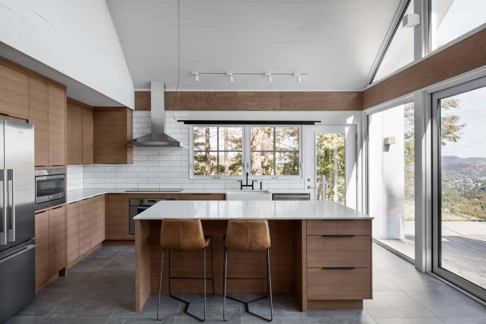 A brown and white kitchen color scheme featuring a tall ceiling and dark gray tiles flooring. It also offers a breakfast bar center island.
