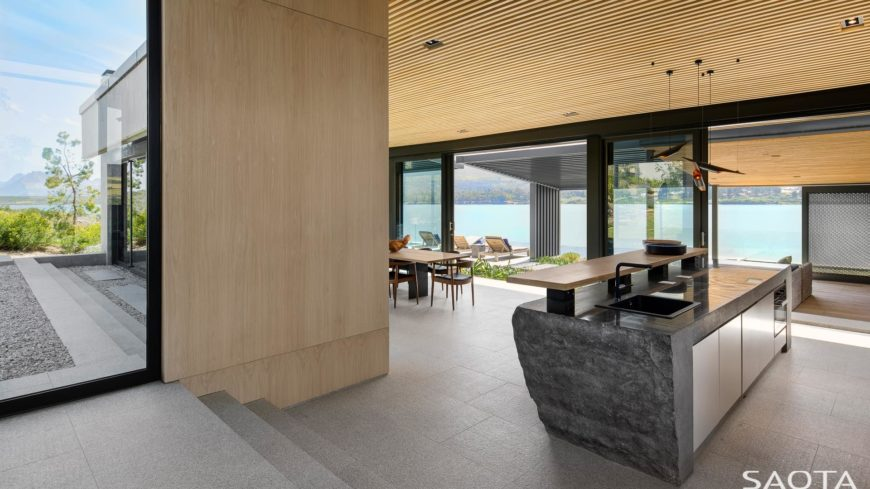 A contemporary house with a single wall kitchen boasting a very stylish center island with a separate counter for a breakfast bar.