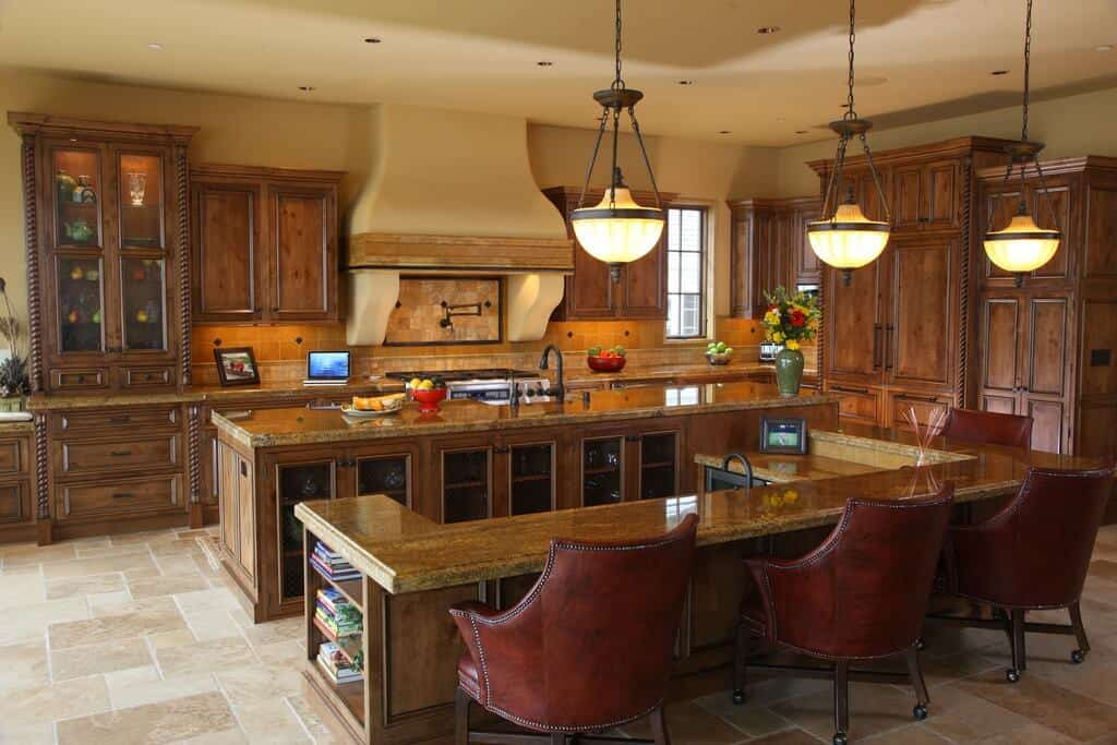 Large kitchen with two islands, both featuring gorgeous countertops, but the other one has a separate breakfast bar counter lighted by pendant lights.