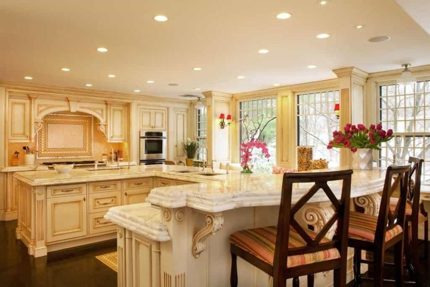 Large kitchen featuring an L-shaped center island and a breakfast bar counter with marble countertops. The area is lighted by recessed ceiling lights.