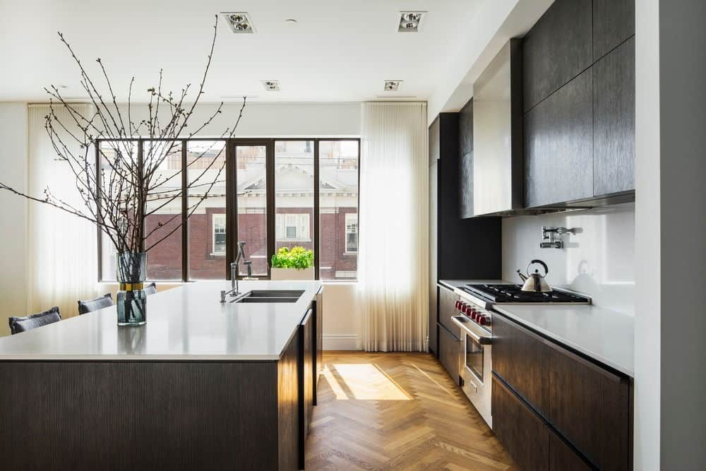 A single wall kitchen featuring herringbone-style hardwood flooring, along with dark brown kitchen counter and center island, both have white countertops.