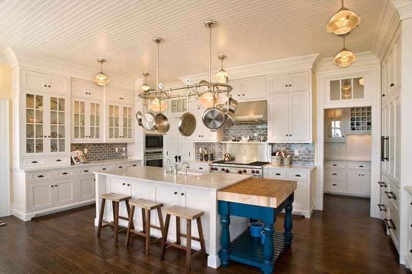 A spacious kitchen featuring classy pendant ceiling lights. It has a center island with a marble countertop and has a breakfast bar.