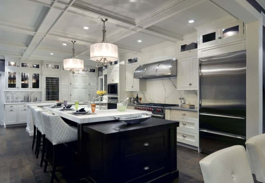 Large modern kitchen with hardwood flooring and a white coffered ceiling. It offers a large center island with space for a breakfast bar featuring a thick marble countertop.