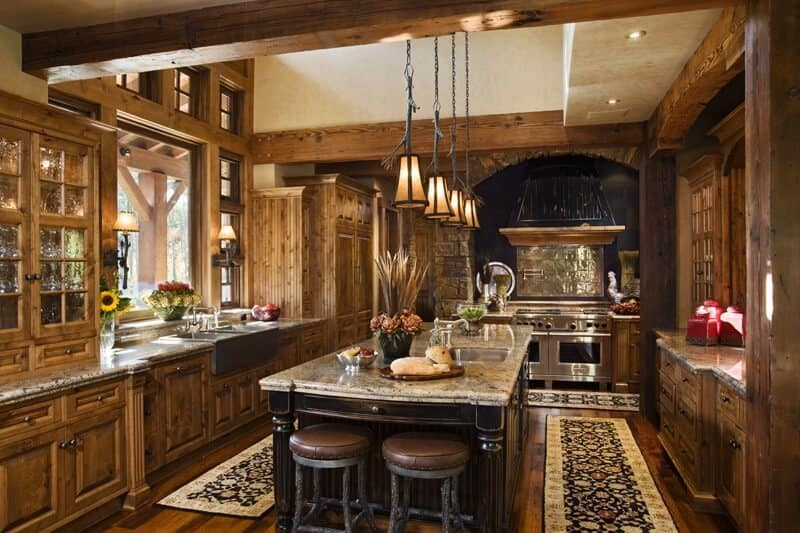 A rustic kitchen featuring marble kitchen countertops and a center island with space for a breakfast bar, lighted by pendant lights.