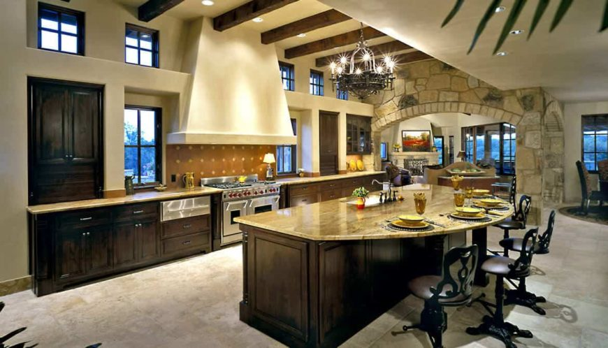 A single wall kitchen with tiles flooring and a ceiling with beams. It also has a massive center island with space for a breakfast bar, lighted by a gorgeous chandelier.