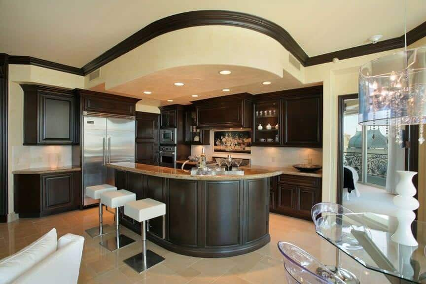 An L-shaped kitchen offering a curved island with a breakfast bar counter paired with modern bar stools. The area's stylish looks stylish as well.