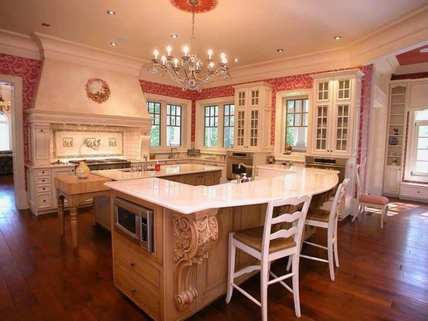 Large kitchen with hardwood flooring and elegant walls. It offers a center island and a breakfast bar counter, lighted by a glamorous chandelier.