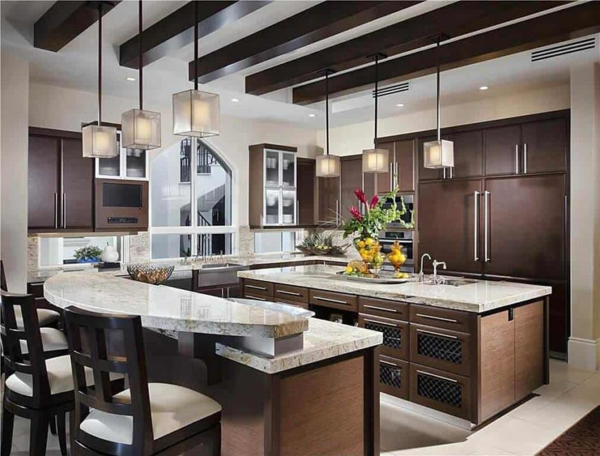 A close up look at this kitchen's breakfast bar counter lighted by pendant lights. The kitchen also has a center island with a marble countertop, lighted by pendant lights as well.