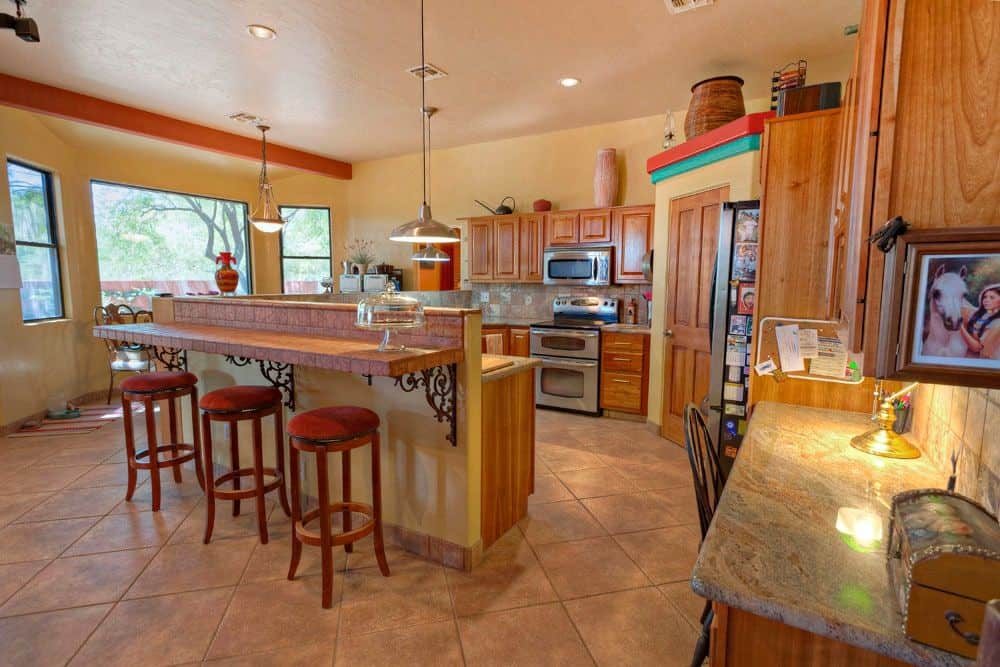 A spacious kitchen featuring tiles flooring and beige walls. It has a breakfast bar counter and a desk on the side, both featuring marble countertops.