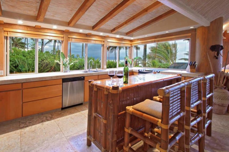A tropical style kitchen with a ceiling with beams and glass windows. It also has a charming breakfast bar island with wooden seats.