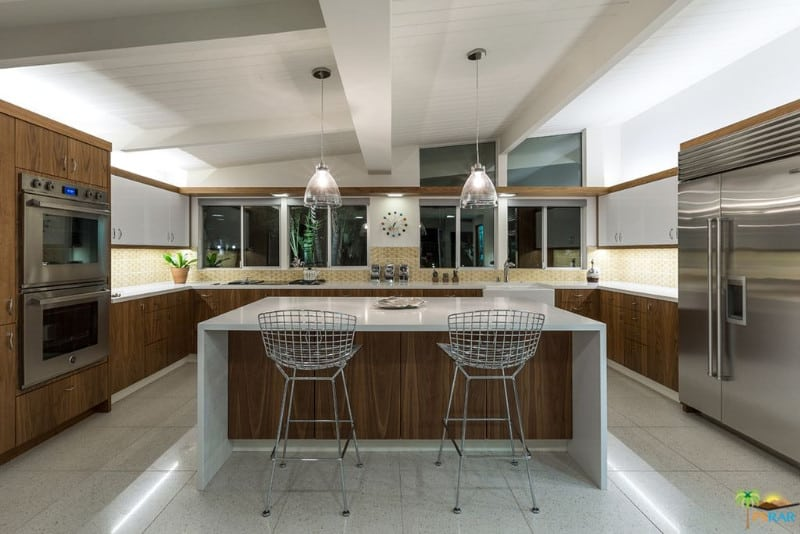 U-shaped kitchen with tiles flooring and a custom ceiling. It has white kitchen counters and a white waterfall-style breakfast bar island lighted by a pair of pendant lights.