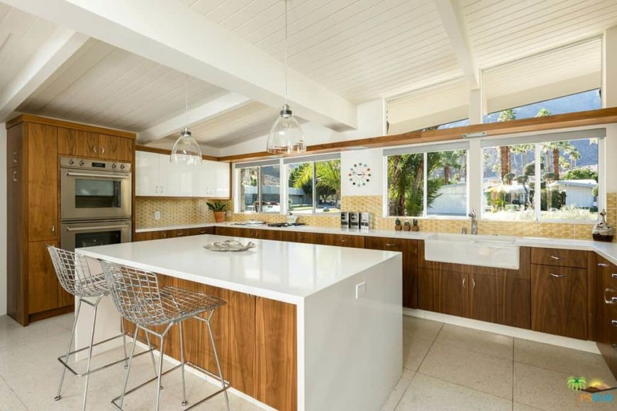 A tropical home with a lovely kitchen featuring a white waterfall-style island with a breakfast bar lighted by pendant lights.