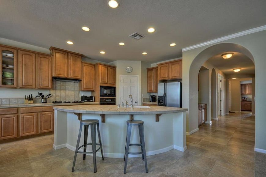 A spacious kitchen with tiles flooring and gray walls, along with a gray ceiling with recessed ceiling lights. The kitchen's island has a breakfast bar as well.