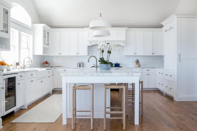 A close up look at this kitchen's island with a marble countertop lighted by white pendant lights. It also has a breakfast bar for four.