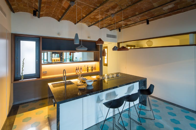 Small kitchen area with charming tiles flooring and an attractive ceiling. It offers a modern kitchen counter and a waterfall-style island with a black marble countertop.