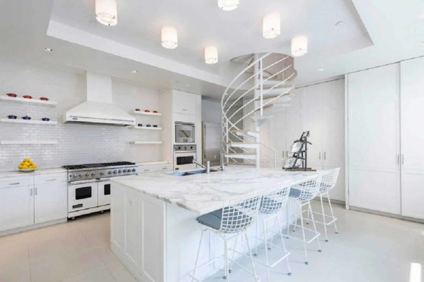 A bright kitchen with white flooring and a white tray ceiling. It has a large marble top island with space for a breakfast bar, lighted by gorgeous set of ceiling lights.