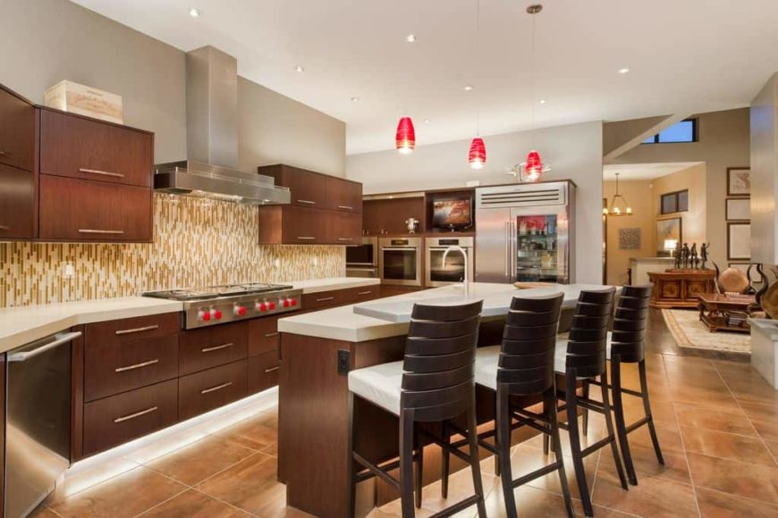 Modern kitchen featuring brown tiles flooring and a white ceiling. It offers a custom breakfast bar island lighted by stylish red pendant lights.