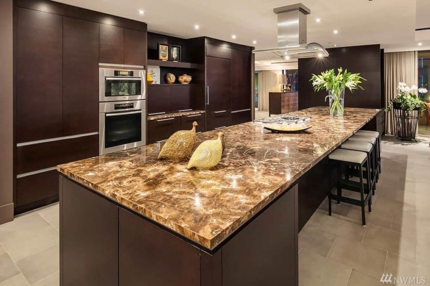 A single wall kitchen boasting a large island with a gorgeous marble countertop and has space for a breakfast bar as well.