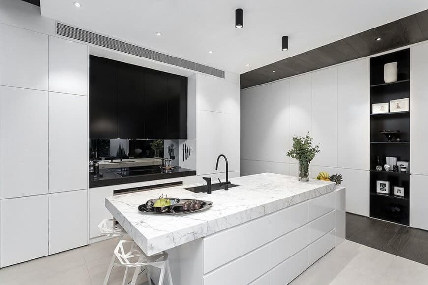 Modern kitchen featuring white walls and ceiling. There's a center island with a breakfast bar featuring a thick marble countertop and built-in shelving on the wall as well.