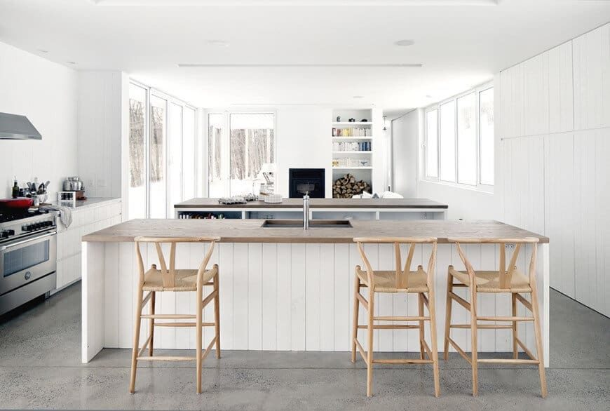 Bright kitchen with white walls and a white ceiling, together with gray flooring. It offers two islands, one serving as a breakfast bar.