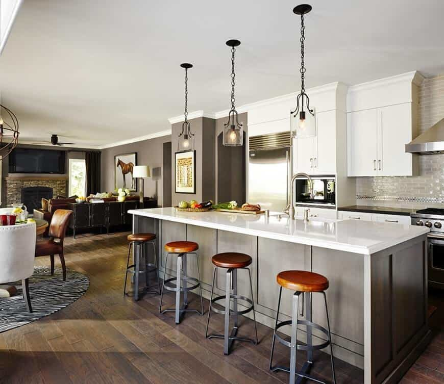 A great room featuring a kitchen with a large center island with a white countertop and has space for a breakfast bar, lighted by pendant lights.