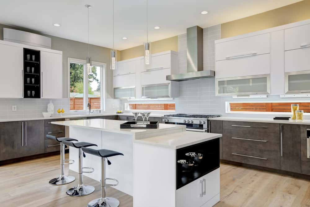 Large L-shape kitchen featuring white cabinetry and gray kitchen counters with white countertops. There's also a center island lighted by charming pendant lights.