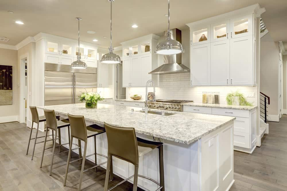 A white L-shaped kitchen with hardwood floors and marble countertops on both kitchen counters and center island. It also offers space for a breakfast bar lighted by pendant lights.