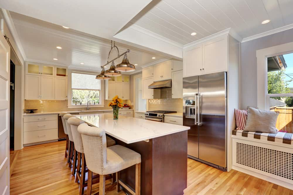 This kitchen features hardwood floors and a white ceiling. It has a center island with a white countertop, along with a breakfast bar lighted by pendant lights.