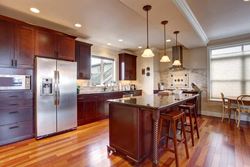 This kitchen features hardwood flooring and brown kitchen counters and cabinetry. It has an island with a granite countertop lighted by pendant lights.