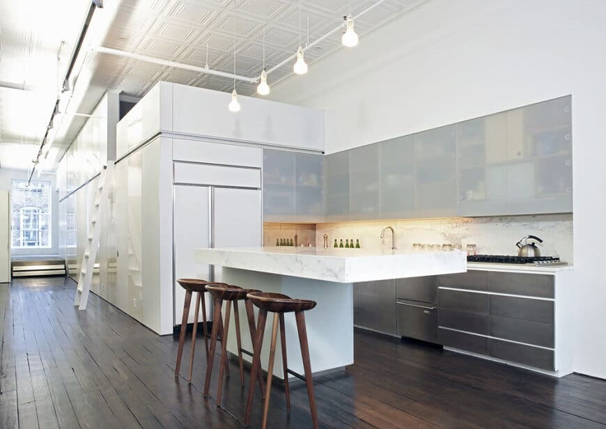 This small kitchen area features hardwood floors, white walls and a white decorated tall ceiling. It offers a thick marble counter on its island.